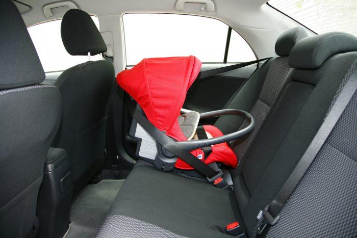 Красное детское автокресло в машине