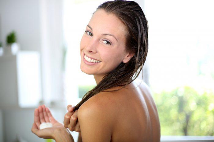 Девушка с мокрыми волосами собирается нанести маску для волос