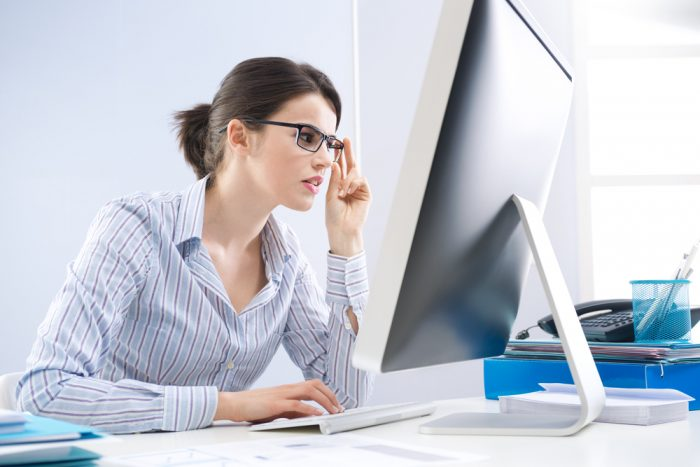 Девушка в полосатой рубашке и в очках сидит перед компьютером