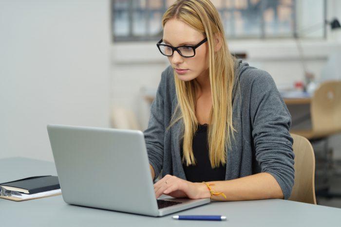 девушка в серой кофте и в очках перед компьютером
