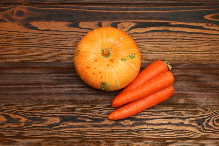Морковь и тыква на деревянной поверхности