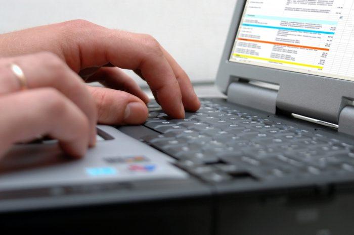 Мужские руки на черной клавиатуре ноутбука
