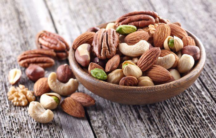 Орехи, фундук, фисташки в деревянной тарелке