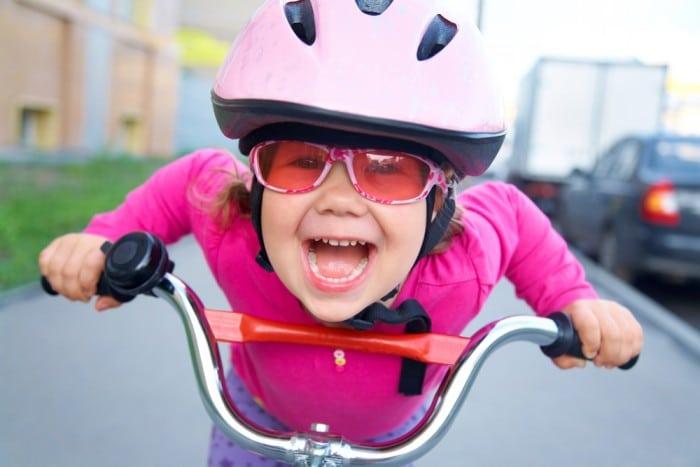 Ребенок на велосипеде в каске и очках