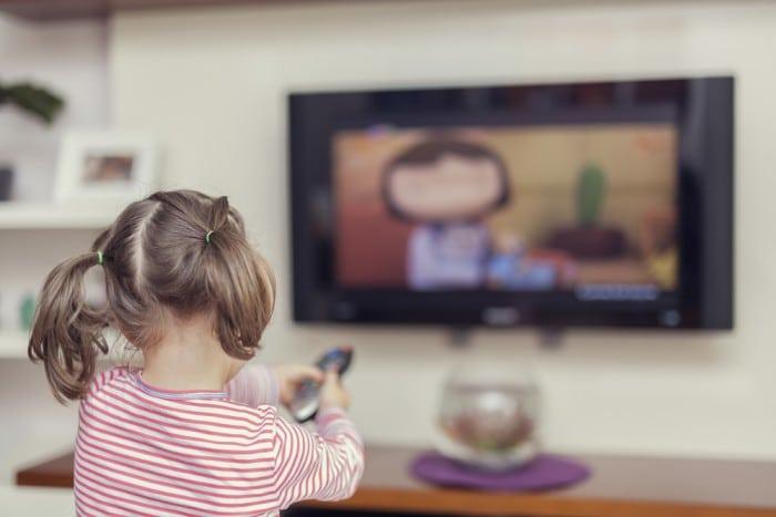 Девочка переключает пультом каналы на телевизоре