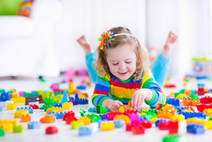 Девочка лежа играет в детский конструктор