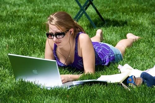 Девушка лежит на траве с ноутбуком