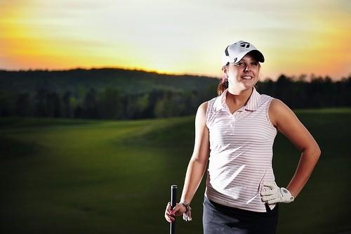 Девушка стоит с клюшкой для гольфа