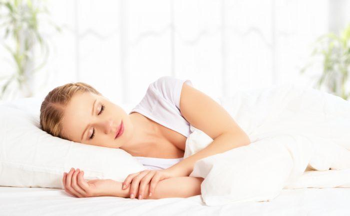 Девушка в белой футболке спит на белой постеле