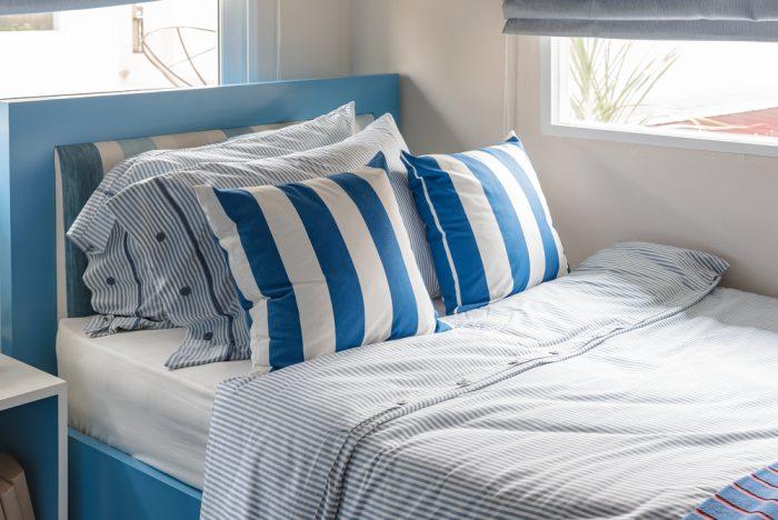 Голубая кровать с полосатыми подушками