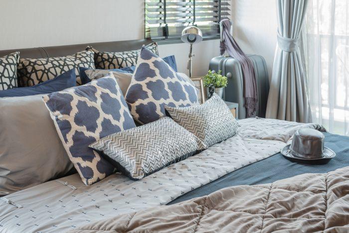 Шляпа лежит на кровати с подушками в спальне