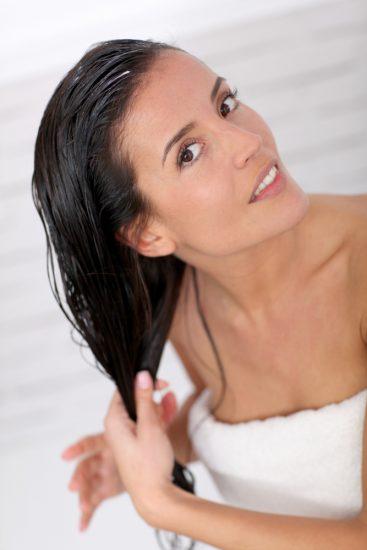 Девушка в полотенце мажет бальзамом волосы