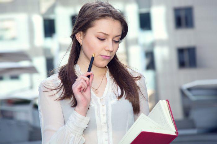 Девушка на улице с блокнотом и ручкой