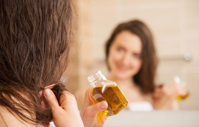 Девушка перед зеркалом с маслом для волос