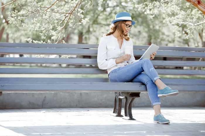 Девушка сидит на лавочке с планшетом