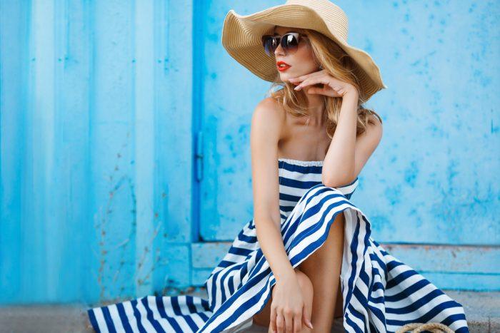 Девушка сидит в большом платье и полосатой шляпе
