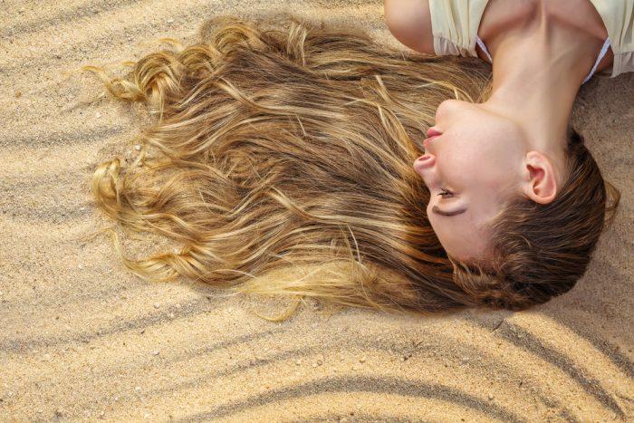 Девушка со светлыми волосами лежит на песке