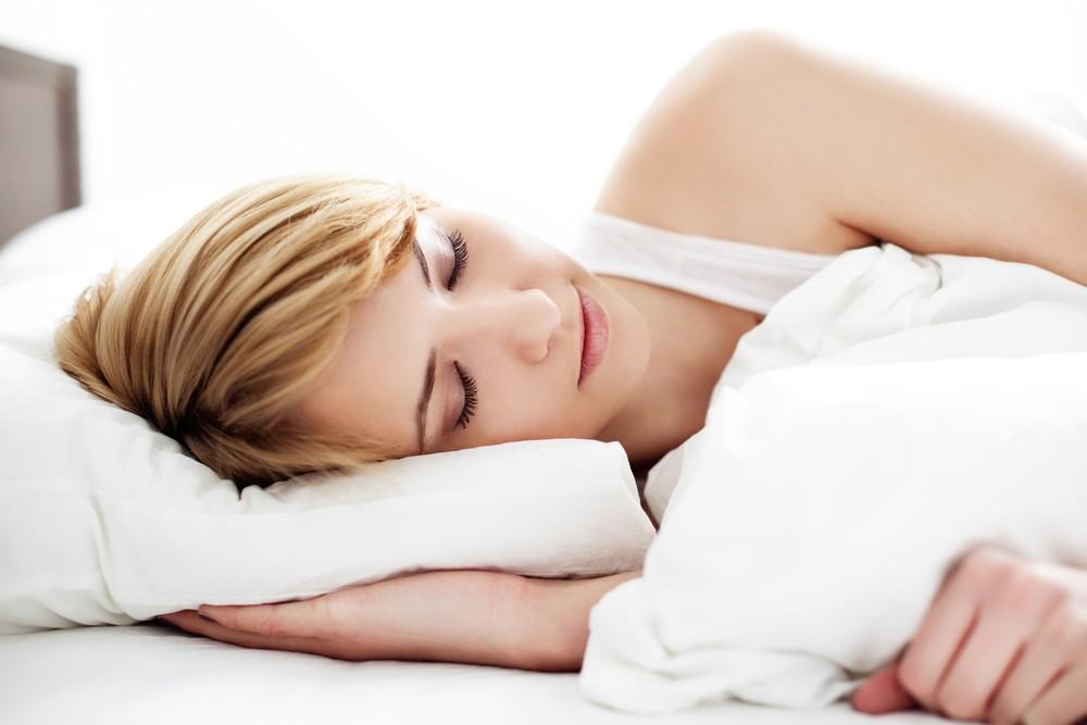 Девушка спит на белой постеле