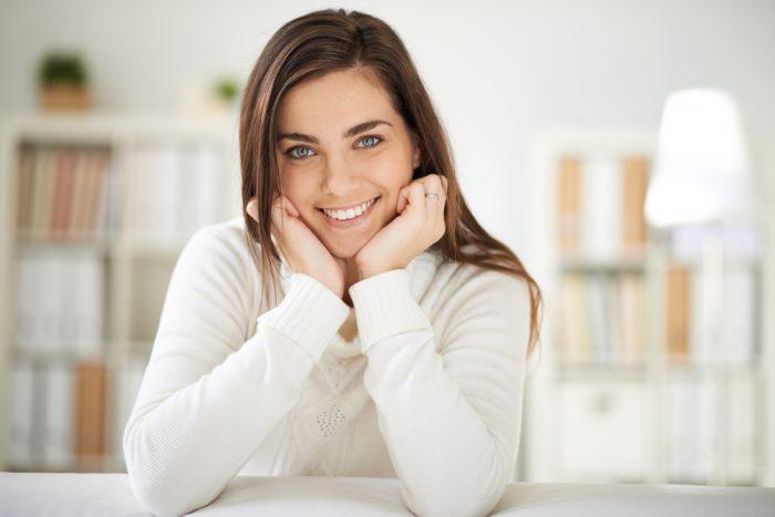 Девушка в белой кофте улыбается сидя за столом