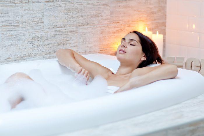 Девушка лежит в ванной с пеной