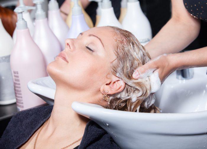 Девушке в салоне моют волосы