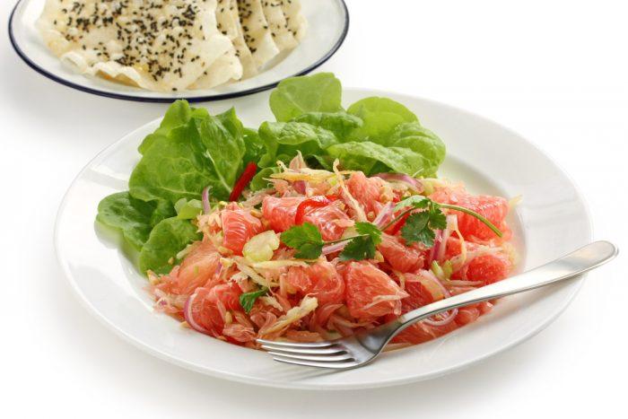 Салат из листьев и помело на белой тарелке