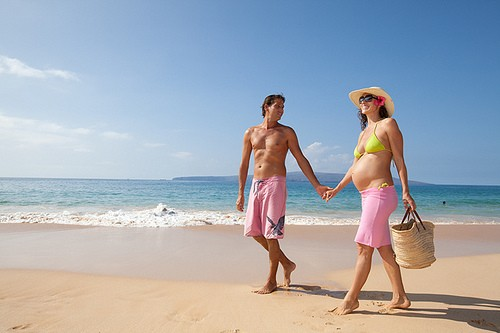 Беременная женщина гуляет по берегу моря
