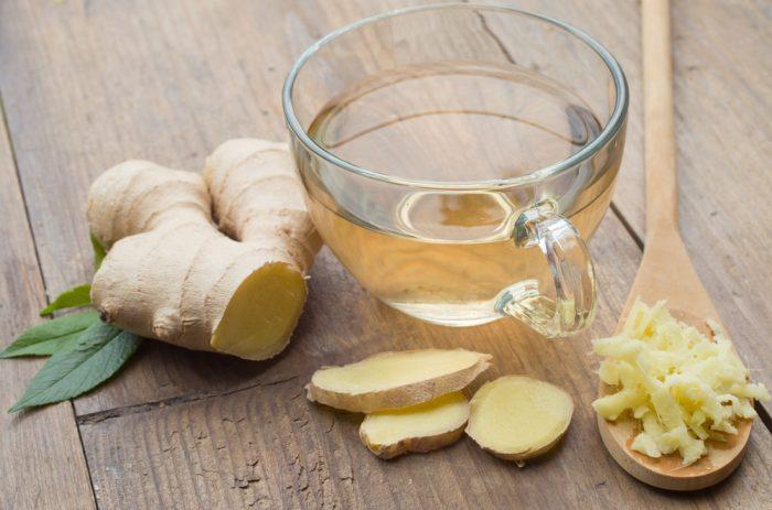 Чашка с имбирным чаем возле имбиря в ложке и на деревянном столе