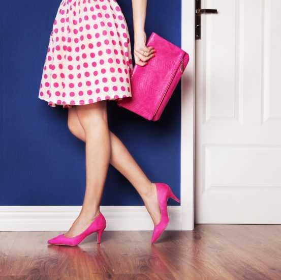 Девушка в розовых туфлях на каблуке и с розовой сумкой