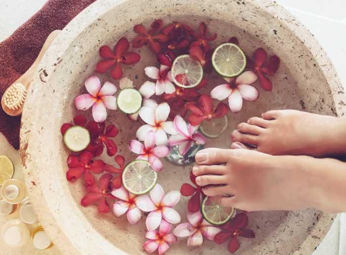 Женские ножки в ванночке с цветами и лаймом