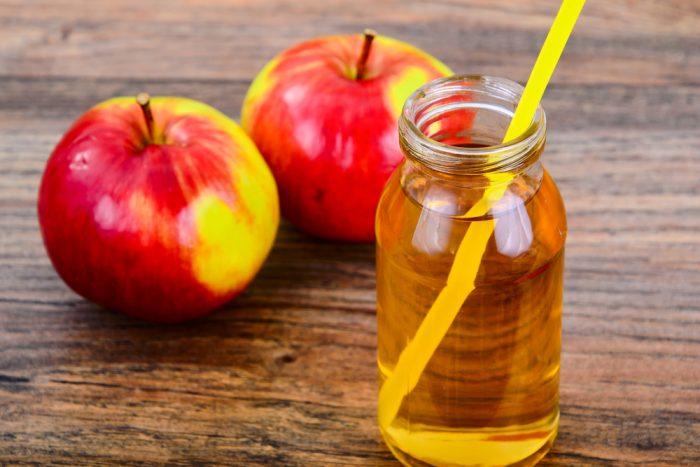 Яблочный сок в банке с трубочкой возле яблок