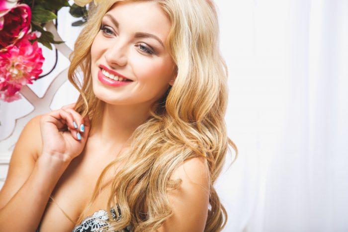 Блондинка улыбается возле цветка