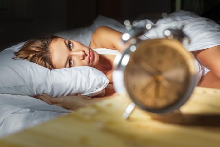 Девушка смотрит на будильник