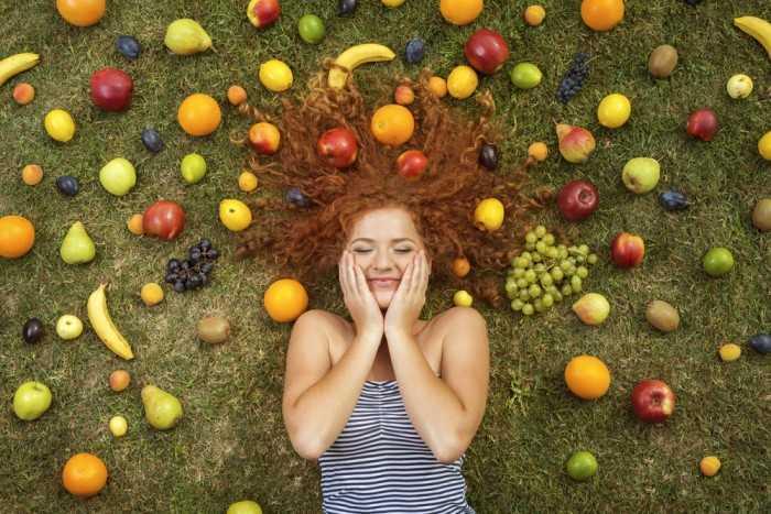 Девушка лежит на полу, вокруг нее фрукты