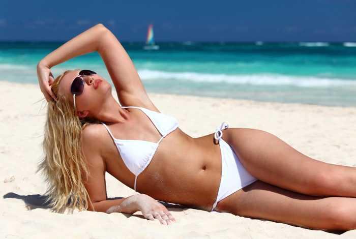 девушка лежит на песке у моря