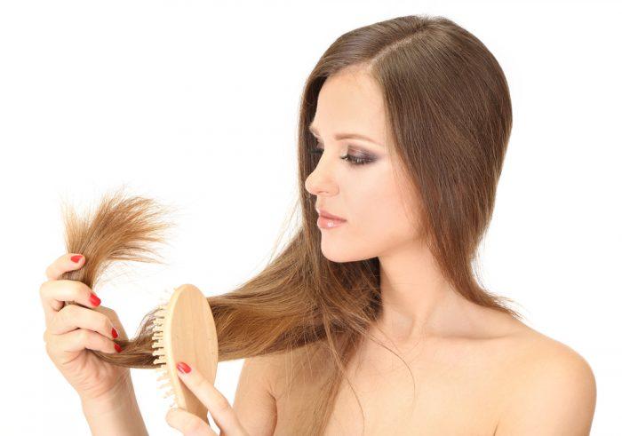 Девушка расчесывает волосы деревянной расческой