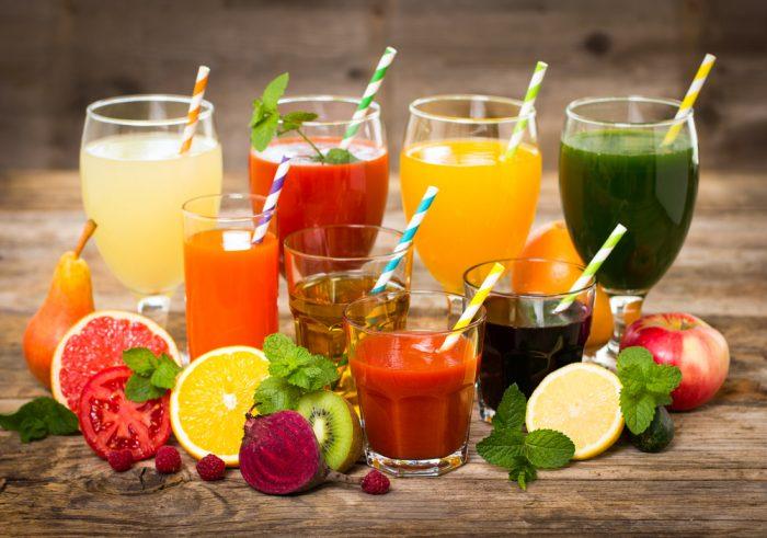 Фруктовые и овощные соки в стаканах с трубочками на деревянной поверхности