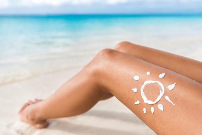 На женской ноге нарисовано солнце кремом