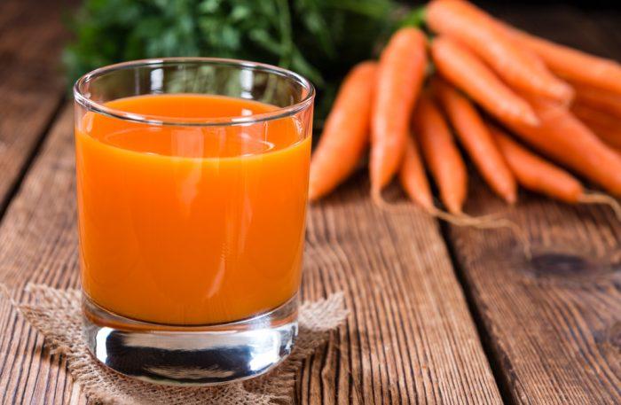 Стакан с морковным соком на столе возле морковки