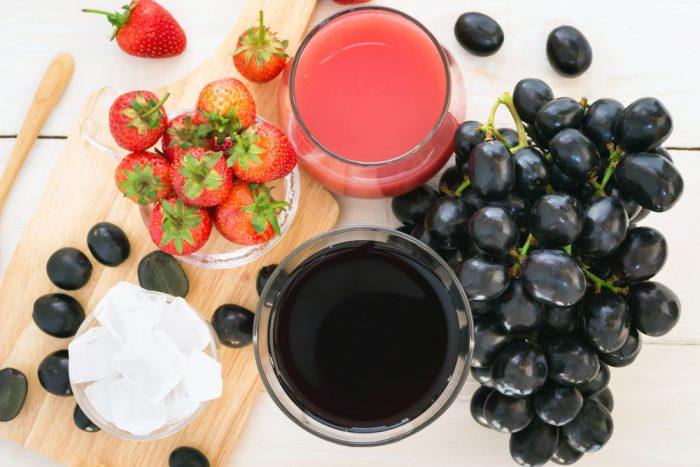 Виноградный и клубничный сок в стаканах на столе