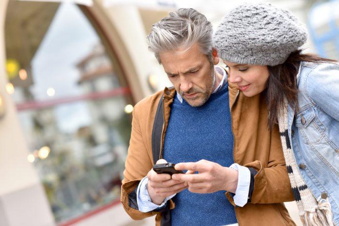 Девушка в сером берете возле мужчины с телефоном