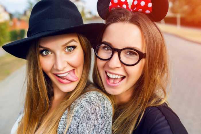 Девушка в черной шляпе и девушка в ушках улыбаются