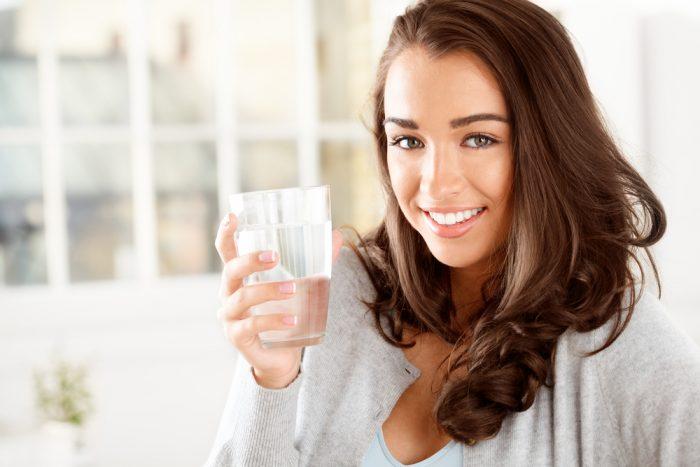 Девушка держит стакан воды