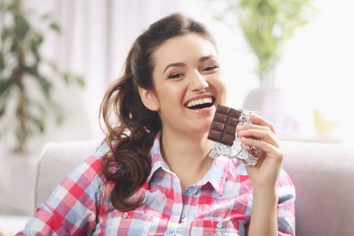 Девушка в клетчатой рубашке ест шоколад