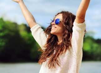Девушка в очках на природе с улыбкой подняла руки