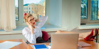 Девушка в офисе в очках положила ноги на стол