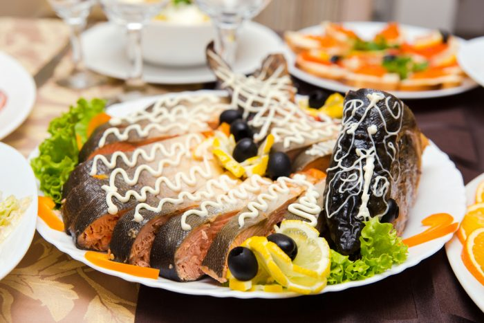 Фаршированная щука на тарелке с лимоном и оливками