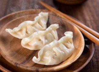 Китайские пельмени на деревянной тарелке с палочками