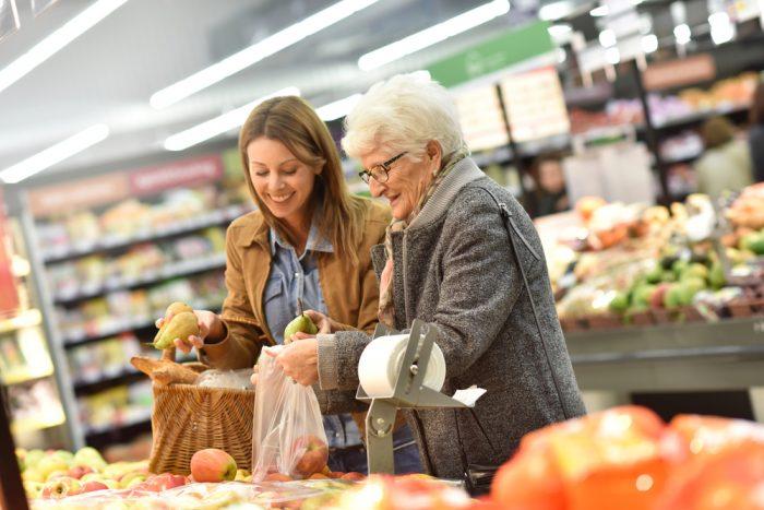 Пожилая женщина с молодой женщиной в продуктовом магазине