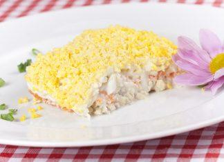 Салат мимоза на белой тарелке с цветком